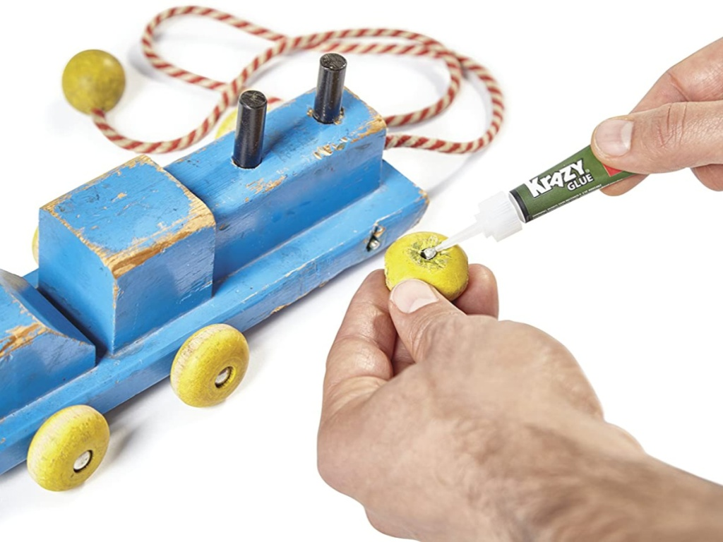 hands putting krazy glue on wheel of broken toy train