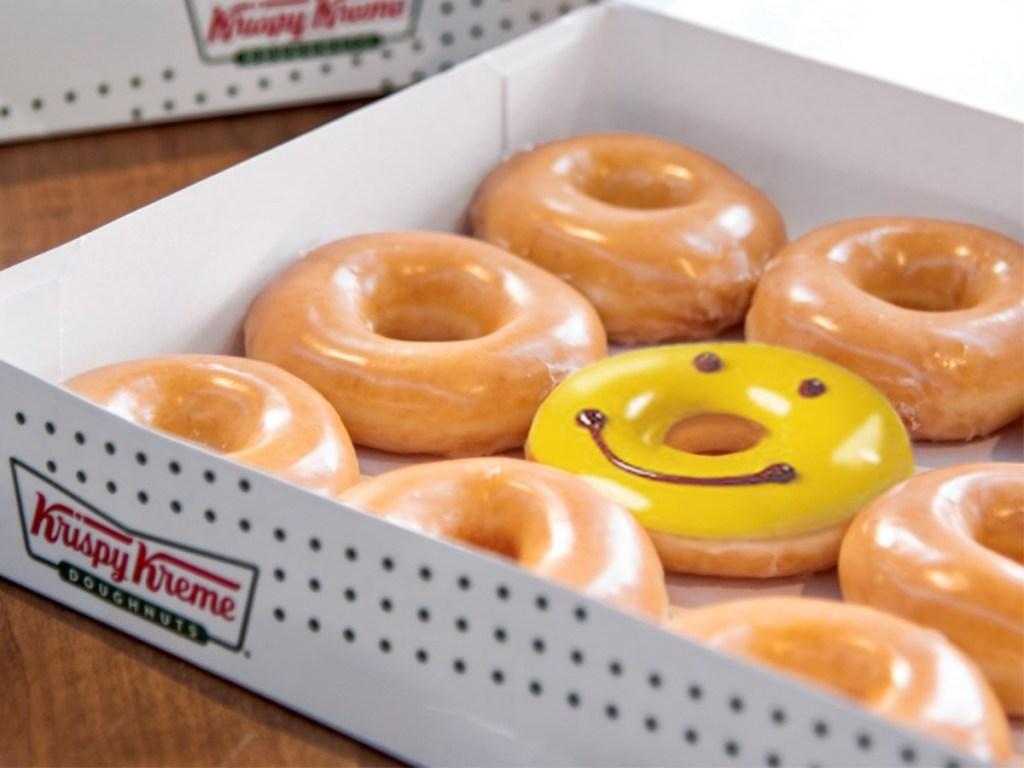 Krispy Kreme donuts with smiling donut in box