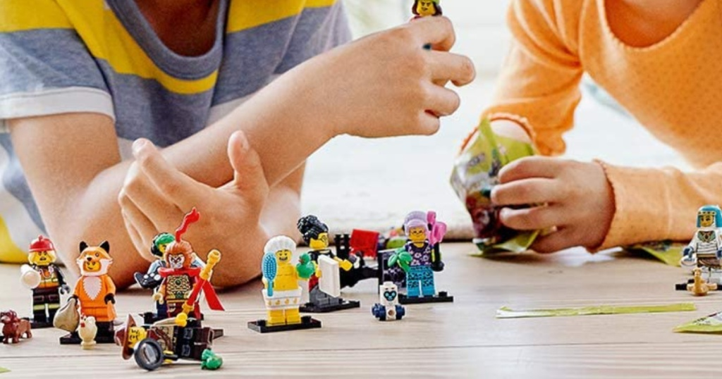 children laying on the floor playing with LEGO mini figures