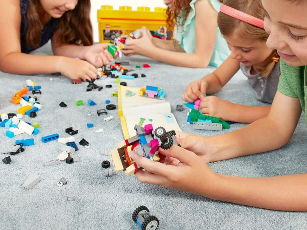 children on carpet playing with building blocks