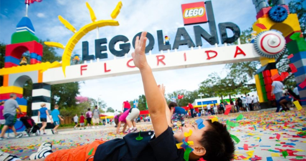 boy playing with LEGOs on ground in front of LEGOLand Florida entrance
