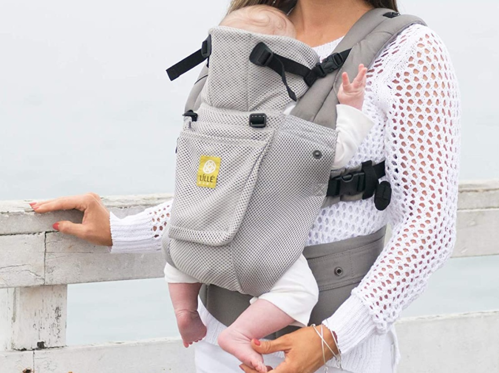 woman holding baby in silver baby carrier leaning on grey rail at beach