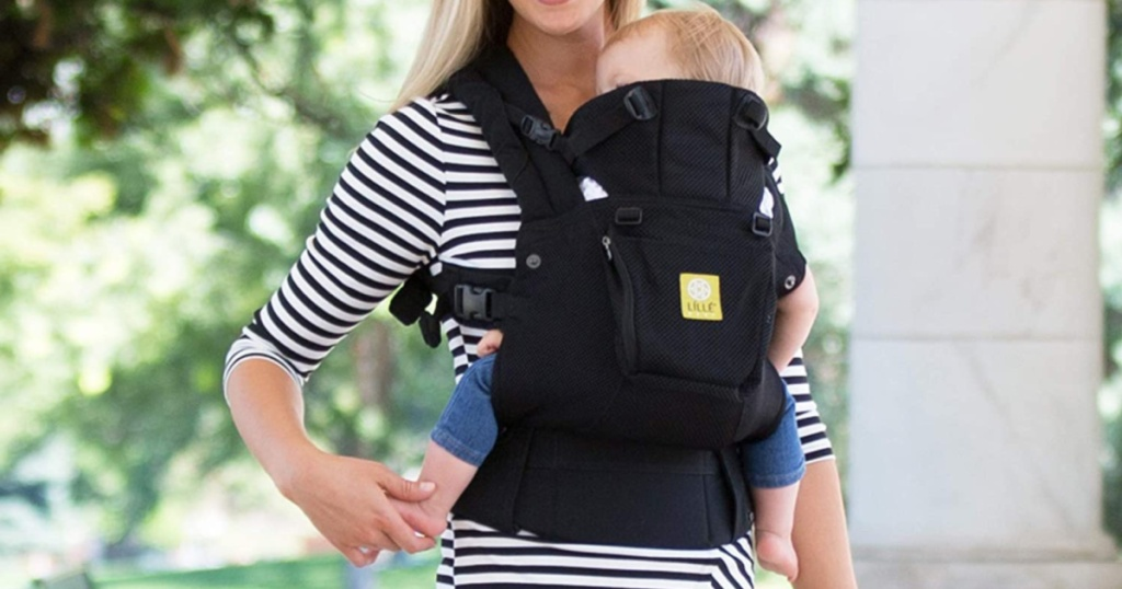 woman in black and white striped dress holding child in black baby carrier