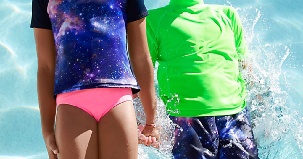 girl in purple and blue galaxy top and pink swim bottoms and boy in blue swim trunks and green rash guard holding hands and jumping into pool
