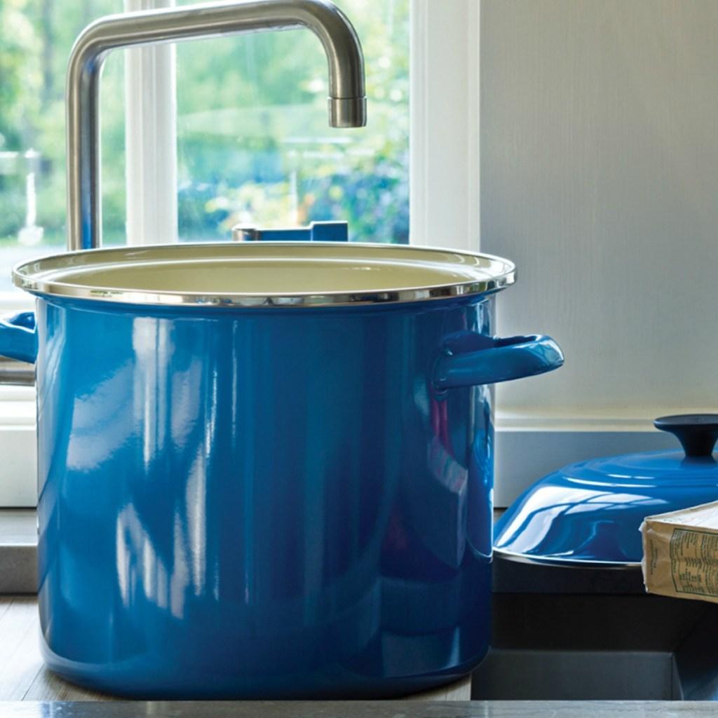 blue LeCreuset stock pot under a sink in a kitchen