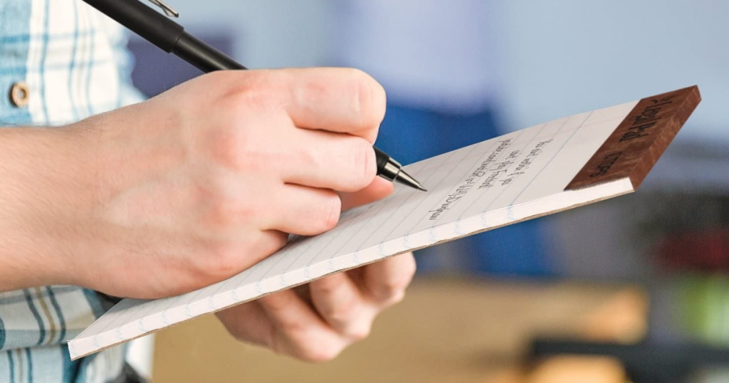 man wearing a plaid shirt holding a legal writing pad writing a note