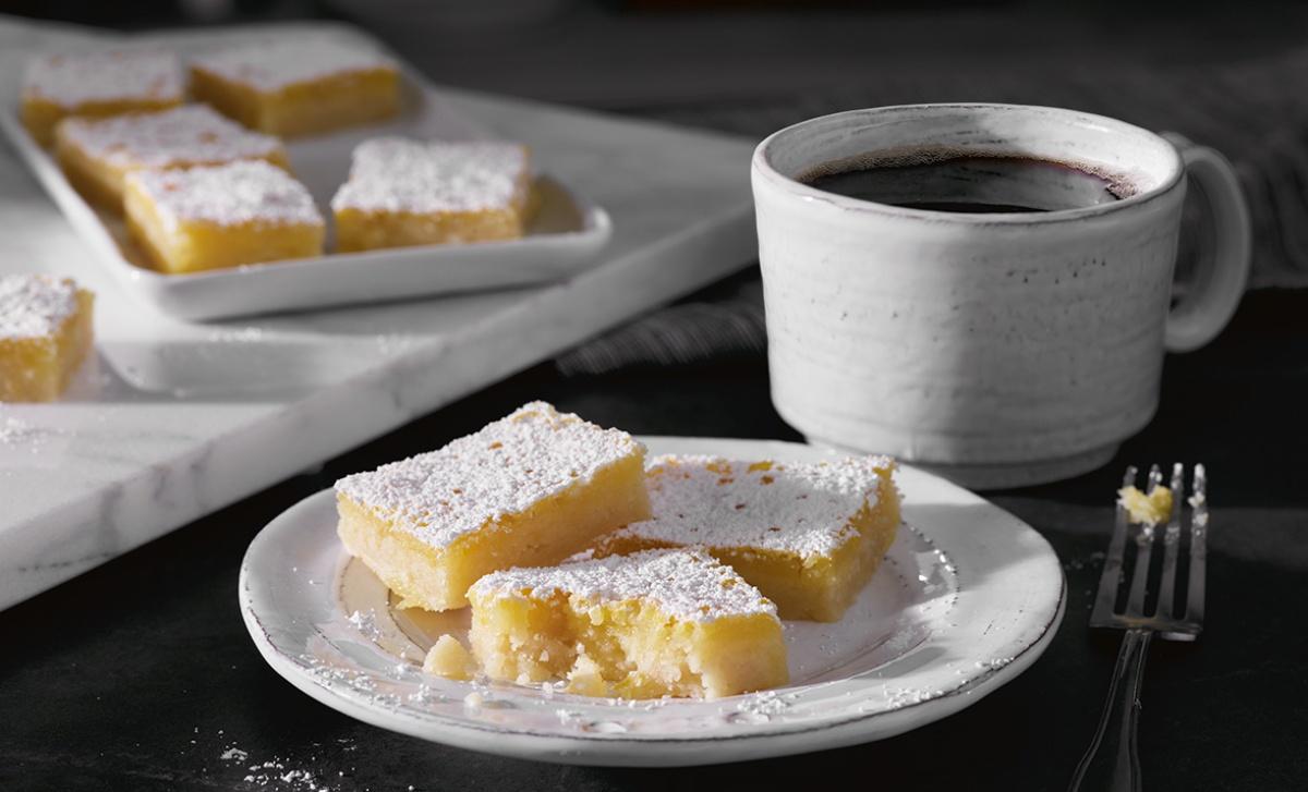 lemon bars on a plate with coffee