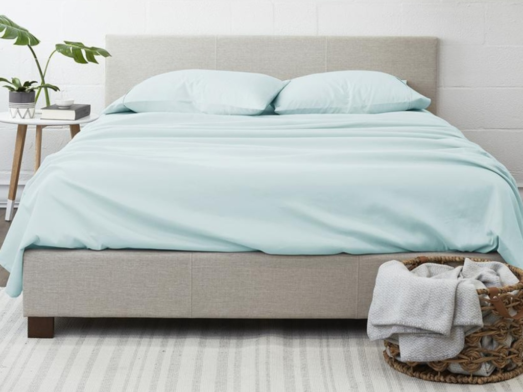 light blue sheets on bed with hamper of clothes in front on floor and side table with plant