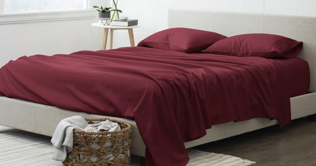 maroon sheets on bed with hamper of clothes and side table