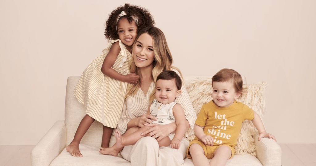 woman sitting on couch with three babys and toddlers in little co by lauren conrad outfits