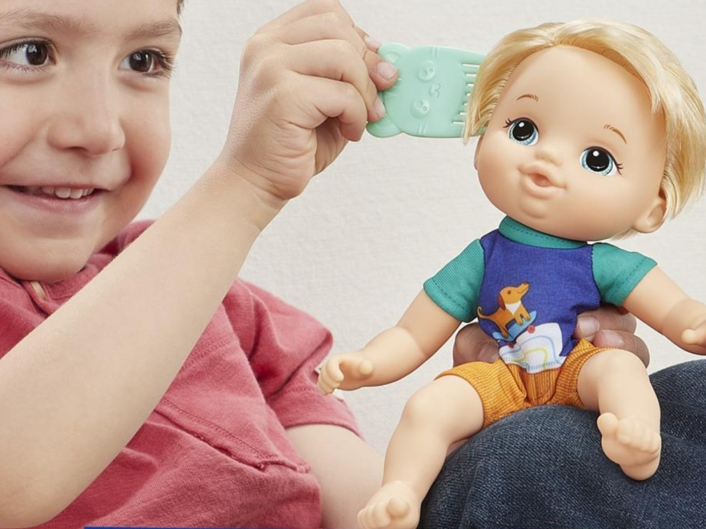 boy brushing hair on blonde doll