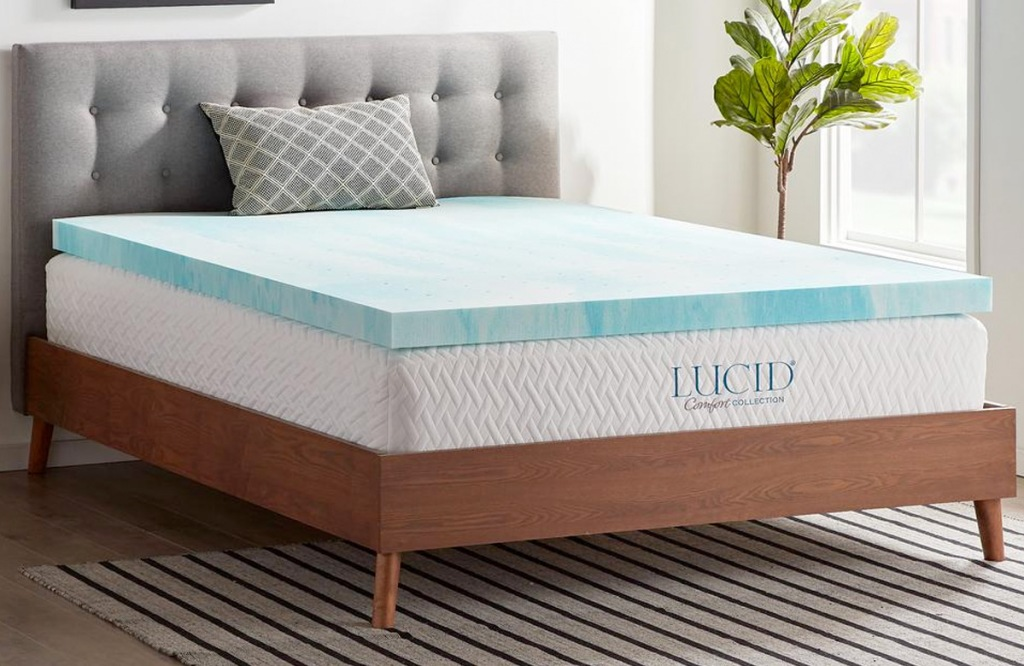 blue and white foam mattress topper on top of white mattress on wooden bed frame in bedroom