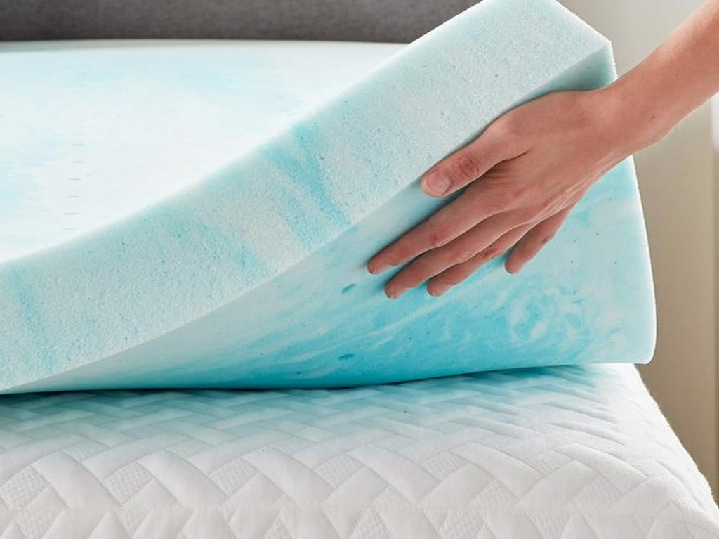 blue and white swirled foam mattress topper with persons hand underneath it