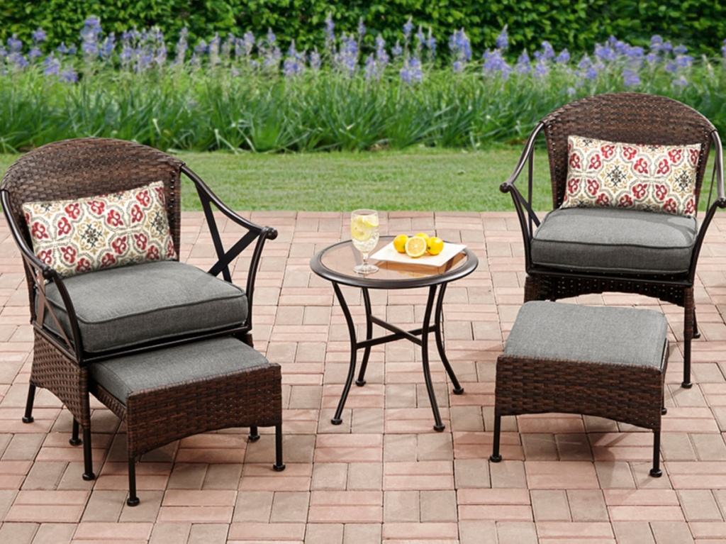 two chairs and ottomans with grey cushions and table on patio outside