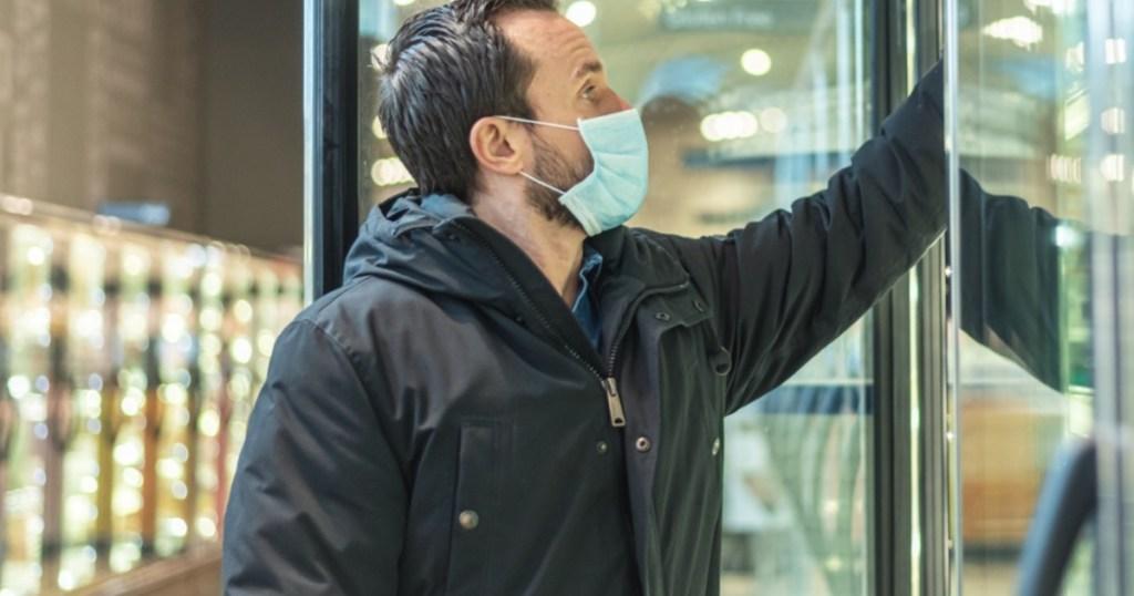 man wearing face mask reaching into freezer in store
