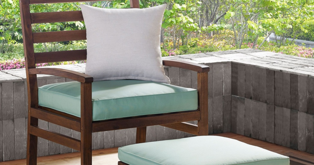 wood patio chair and ottoman with teal cushions on patio