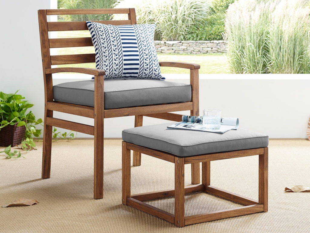 wood patio chair and ottoman with gray cushions on patio
