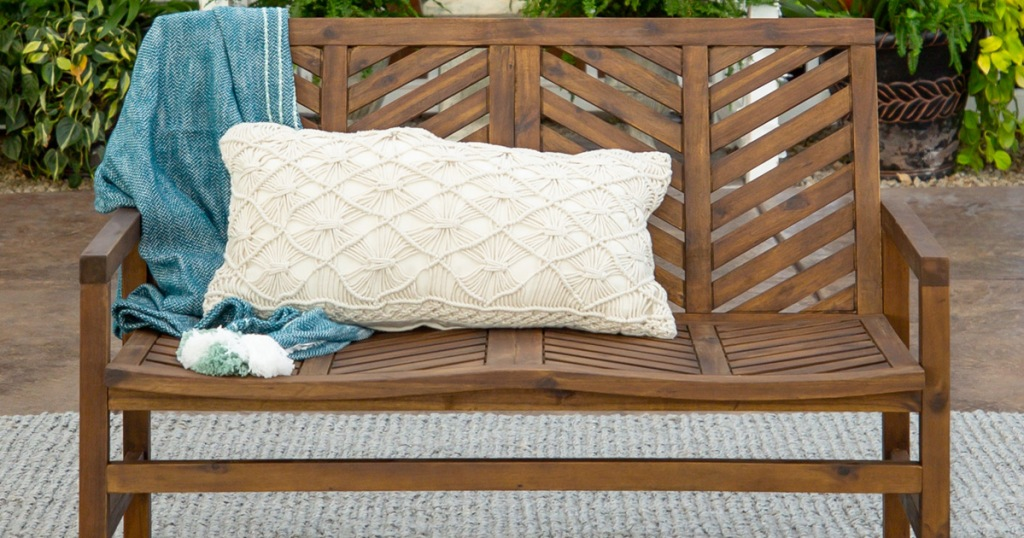 brown wood patio loveseat with chevron patterned back and throw pillow and blanket