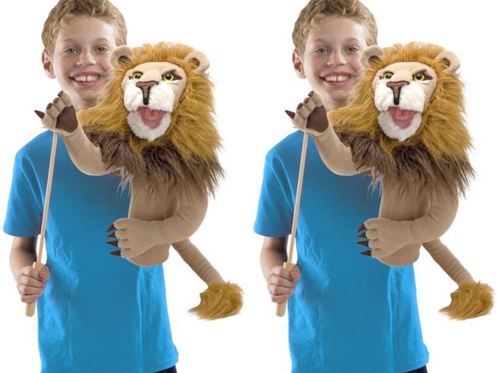 boy holding Melissa & Doug Rory the Lion Puppet