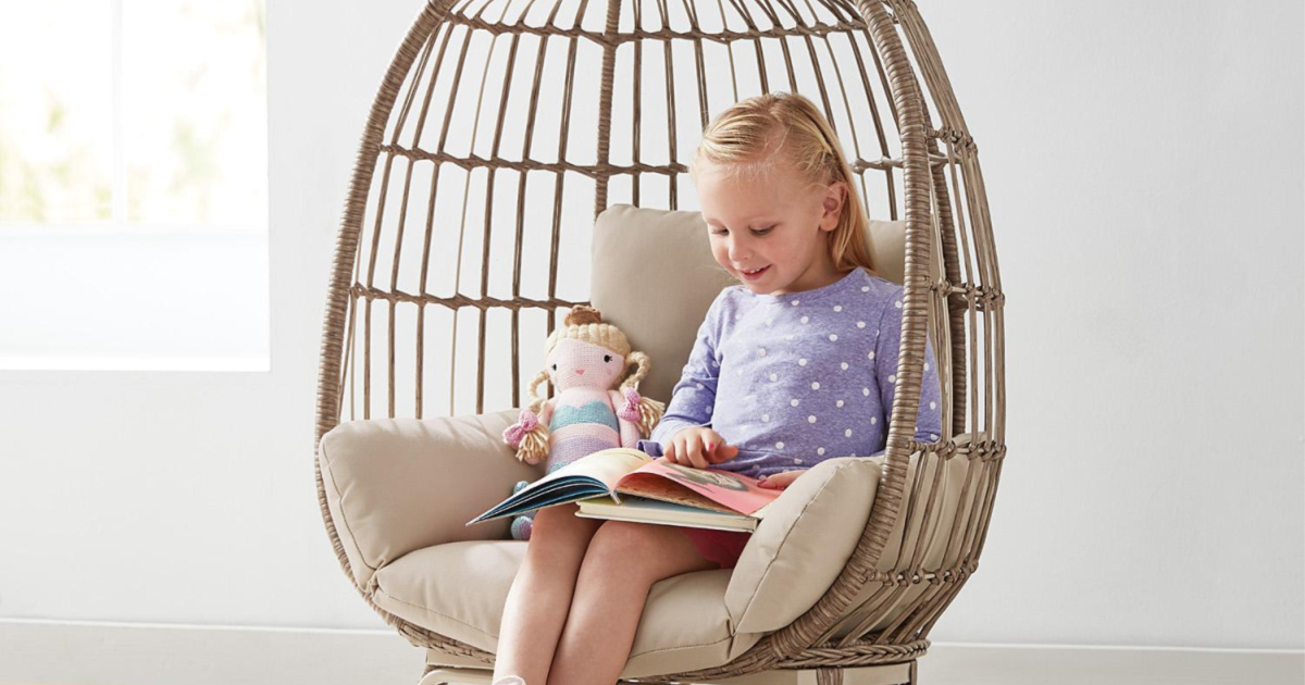 girl reading book in tan egg chair with tan colored cushion