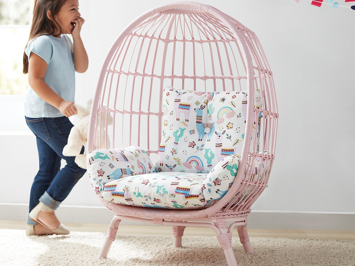 girl walking towards pink egg chair with blue and white patterned cushion