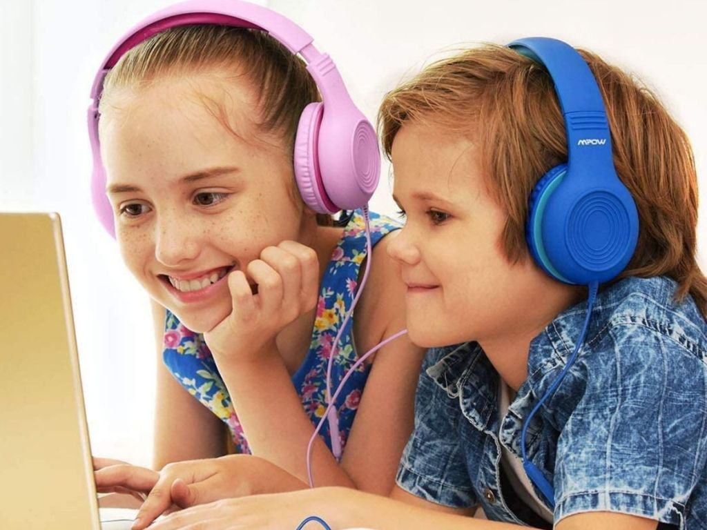 two kids watching a laptop wearing over ear headphones