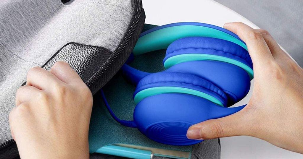 shild putting folding headphones in backpack