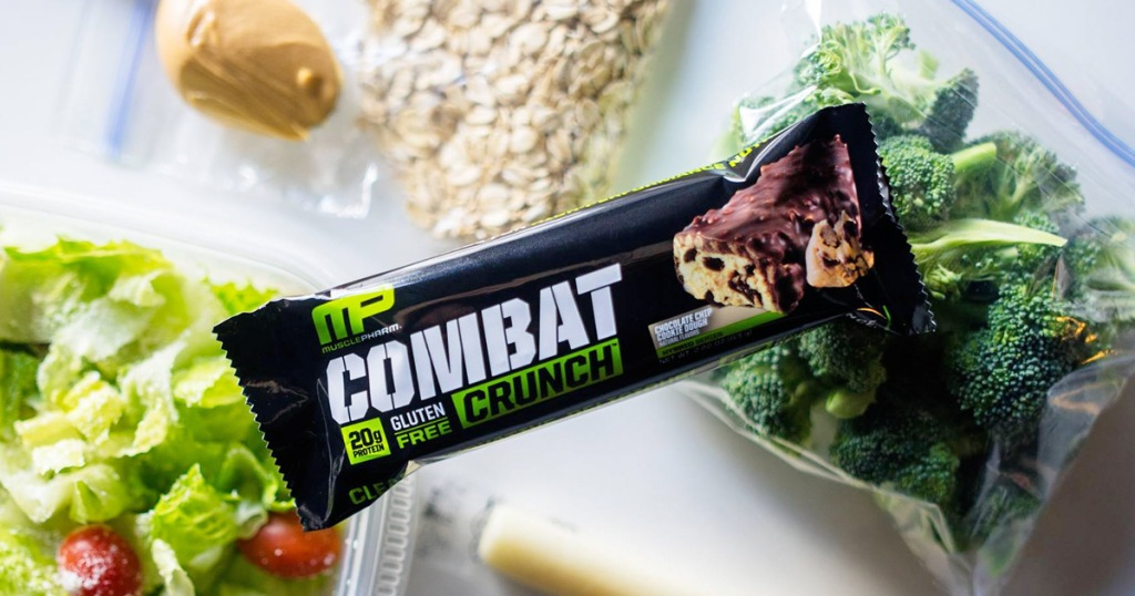 musclepharm protein bar sitting on top of bowl of salad and broccoli
