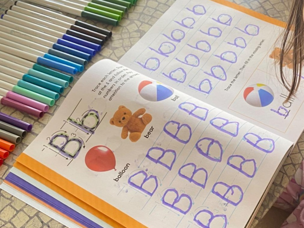 child using learn-to-write book on table with colored markers