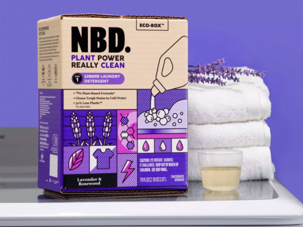 box of NBD Lavender & Rosewood Liquid Laundry Detergent with cup fill of laundry detergent and 3 folded white towels