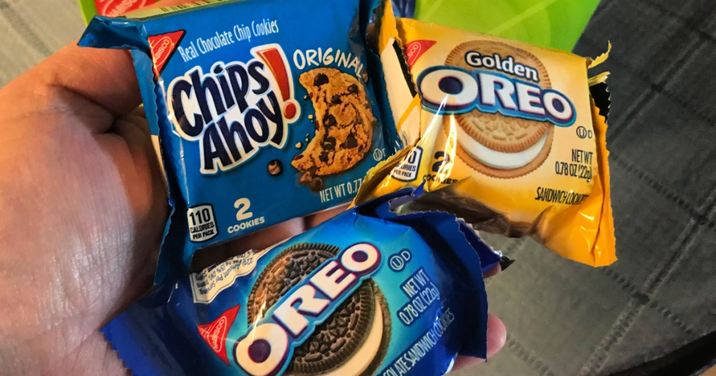 hand holding nabisco cookies chips ahoy, golden oreos, and regular oreos