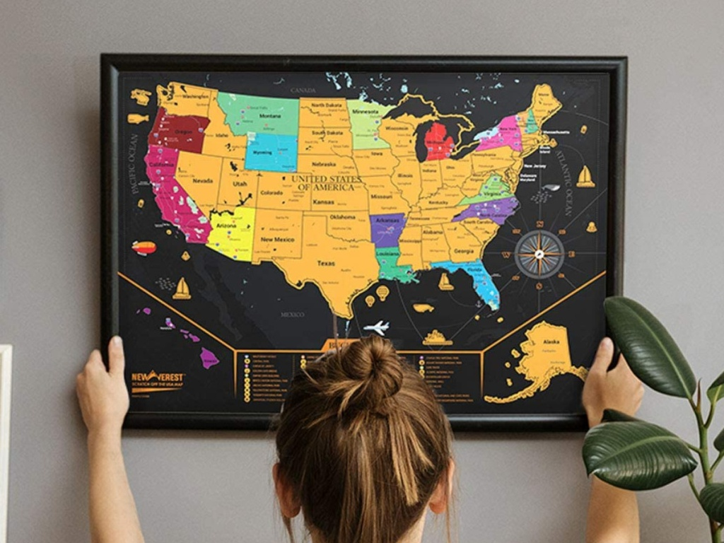 woman hanging framed scratch off US map on wall