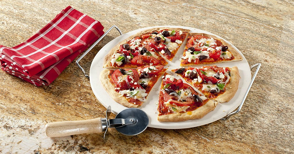 pizza on a stone with a pizza cutter and towel next to it