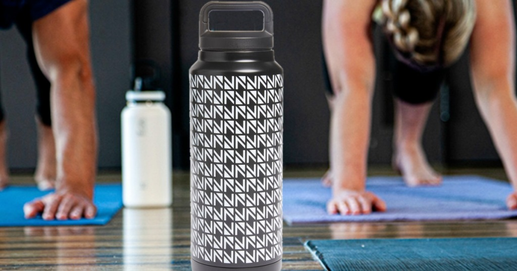 black and white abstract printed metal water bottle on floor in front of people doing yoga