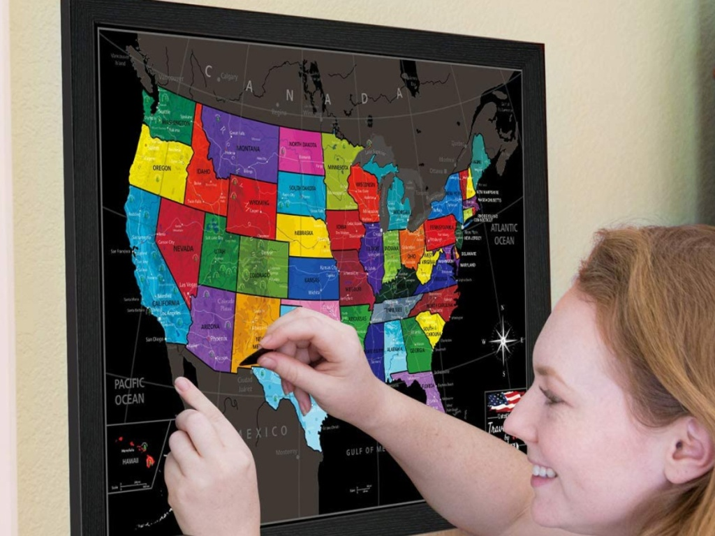 woman using framed scratch off US map on wall