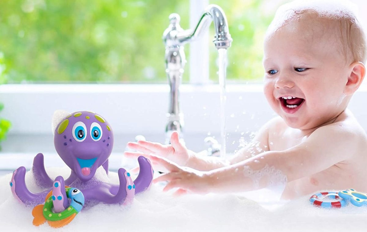 baby in bath in sink playing with purple octopus toy