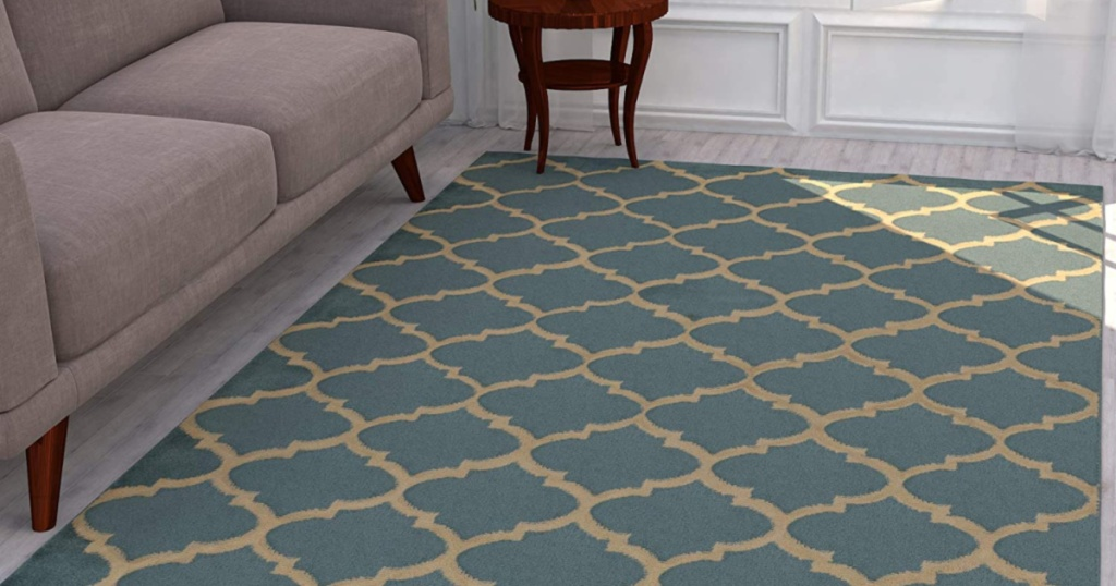 green and cream trellis patterned area rug in living room