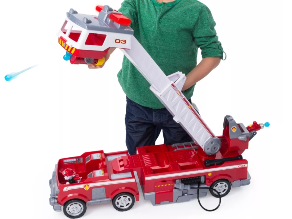 little boy playing with big paw patrol fire truck