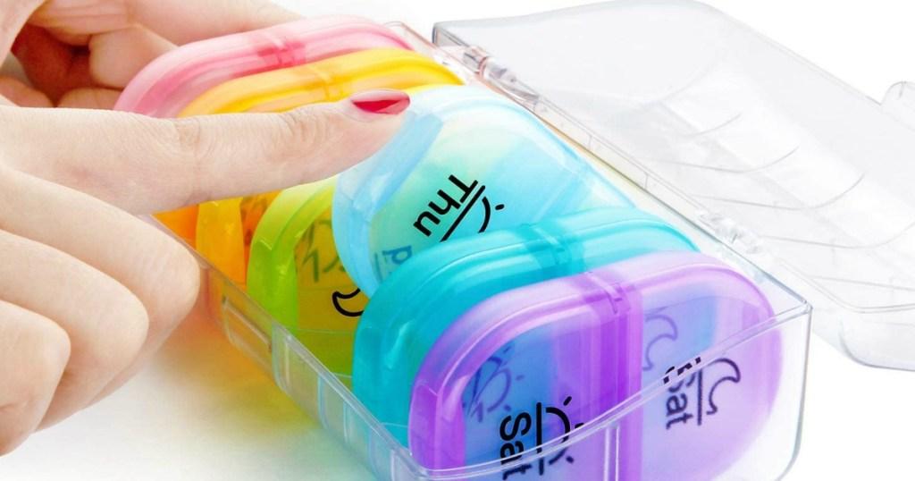 hand putting a case in a pill organizer