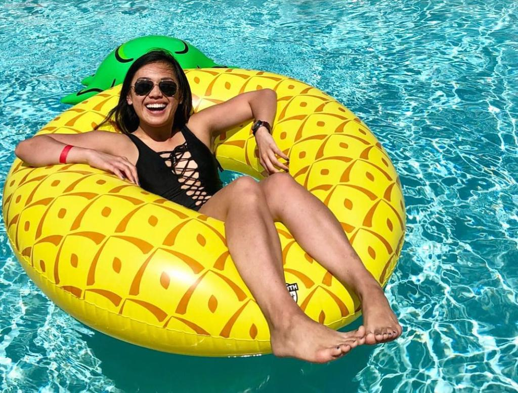 person laying on a pineapple pool float