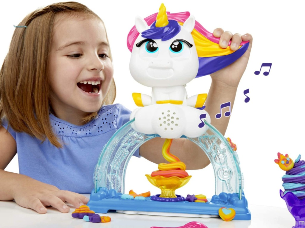 little girl playing with a unicorn play-doh set that is playing music