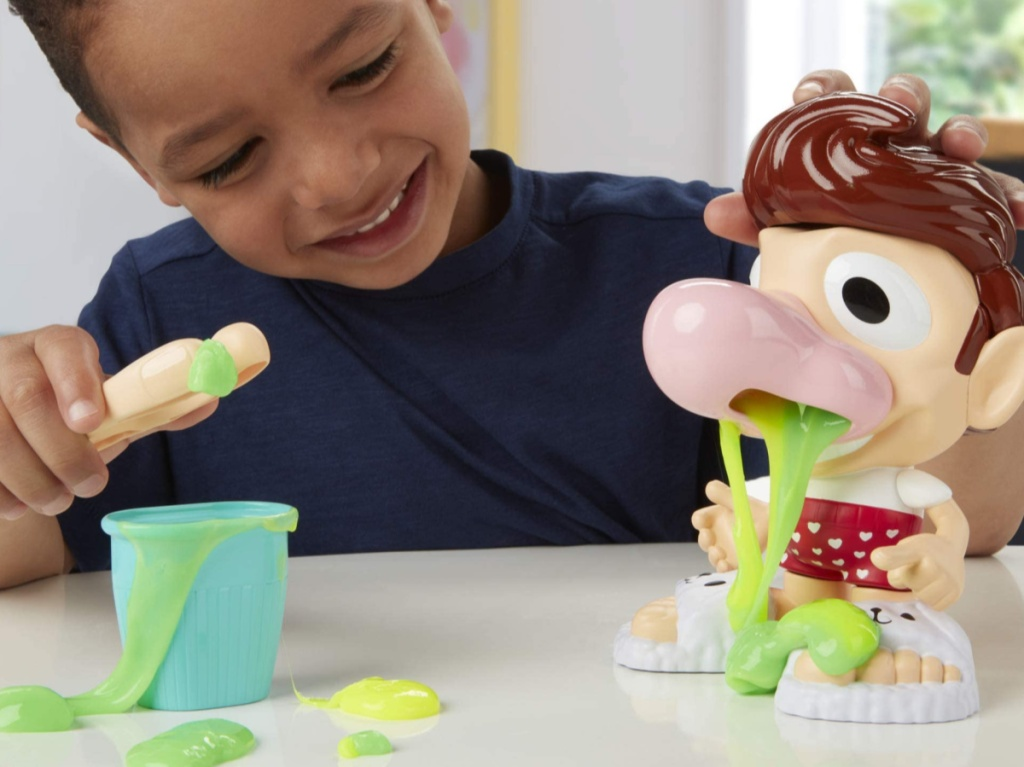 little boy playing with a snotty play-doh set