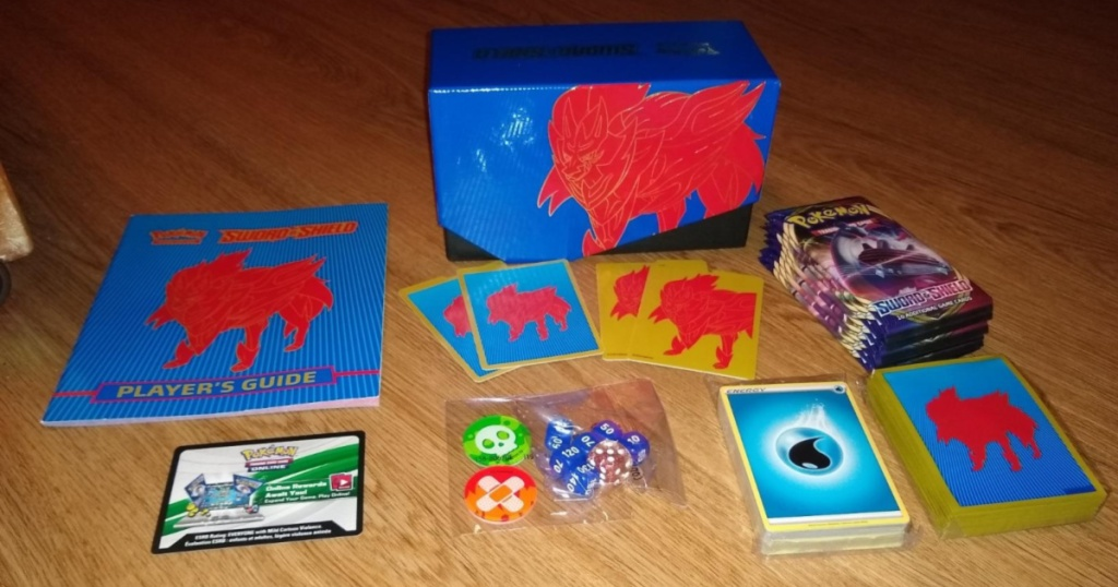 box of Pokemon Trading Card Game: Sword and Shield Elite Trainer Box with cards wrapped up
