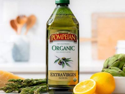 bottle of olive oil with lemons and asparagus on counter in kitchen
