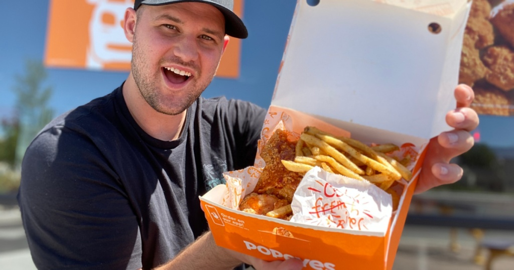 man in front of fast food restaurant holding open box of food