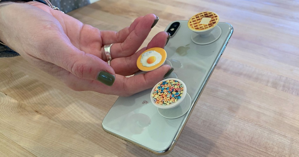 person holding iphone by breakfast themed mini popsockets