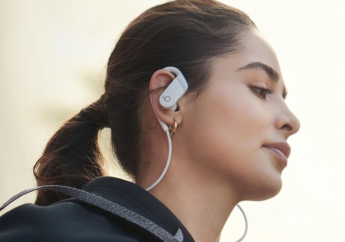 woman wearing a pair of powerbeats earphones that wrap around her ear