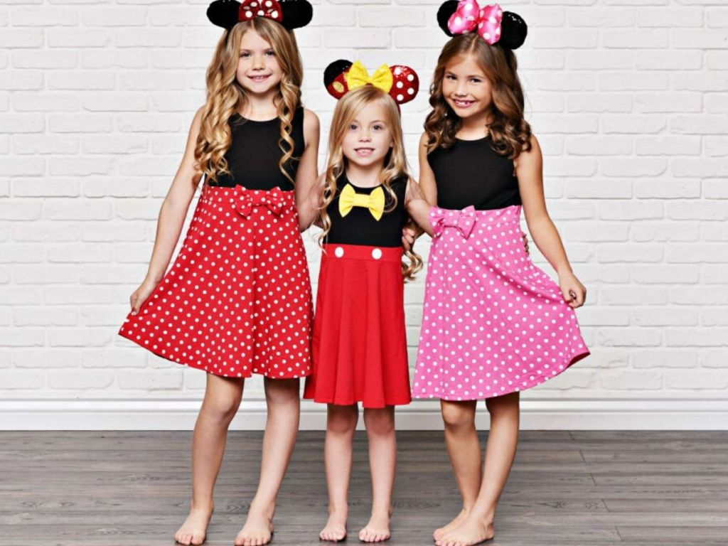 Three girls wearing minnie and mickey inspired dresses