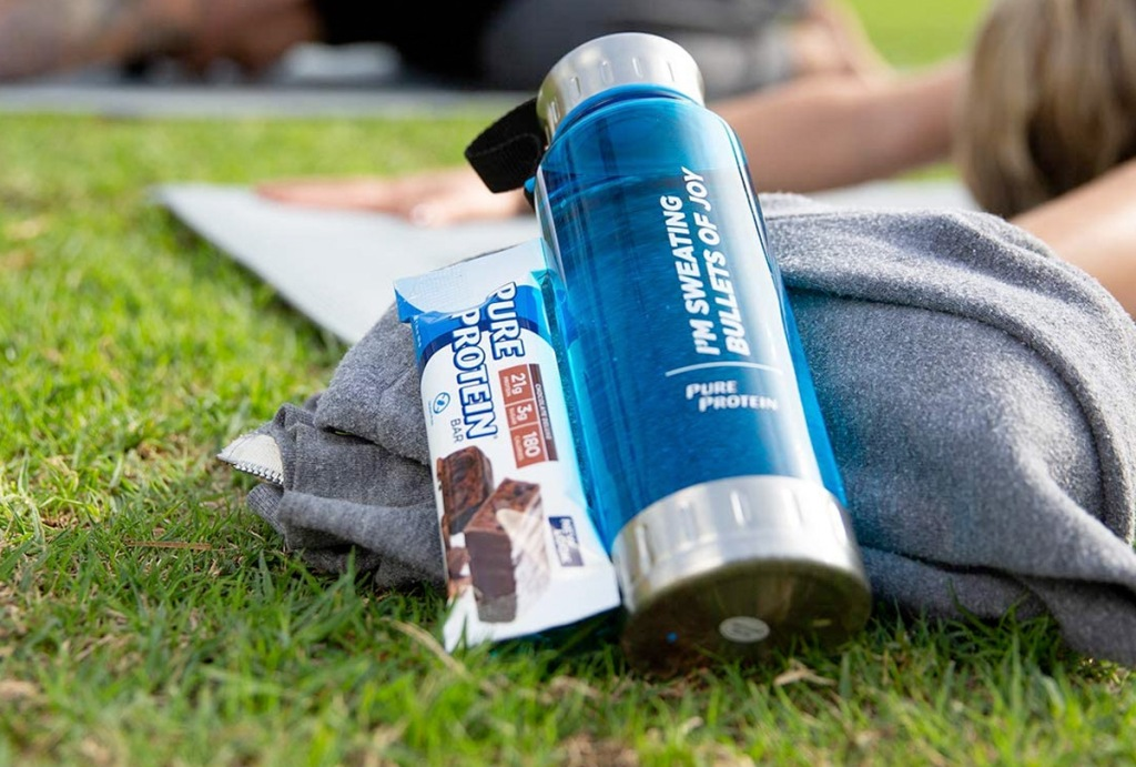 Pure Protein Bar sitting next to backpack and water bottle