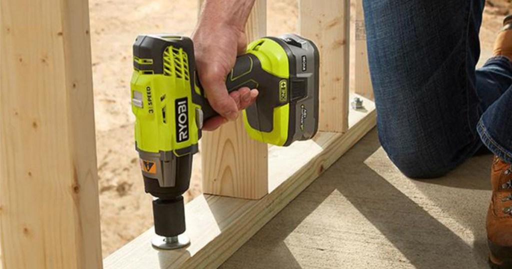man using RYOBI wrench on wood beam